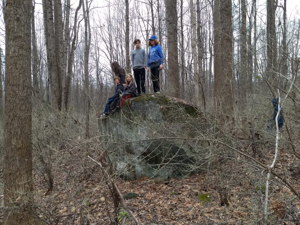 a group of 5 campers sit and stand on a large rock that  is taller than they are