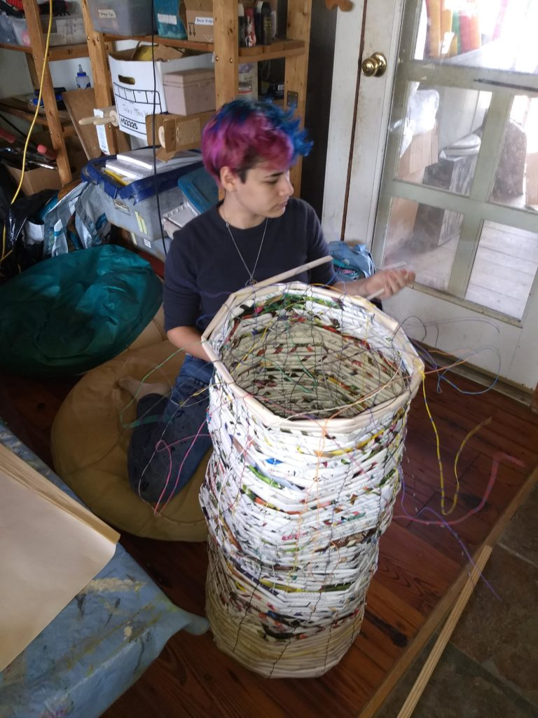 teenaged girl with purple and blue hair works on a basket that is at least 3 feet tall
